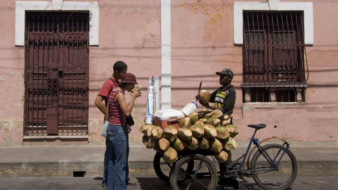 Coconut salesman on his bicycle in front of colonial building, Santo Domingo.